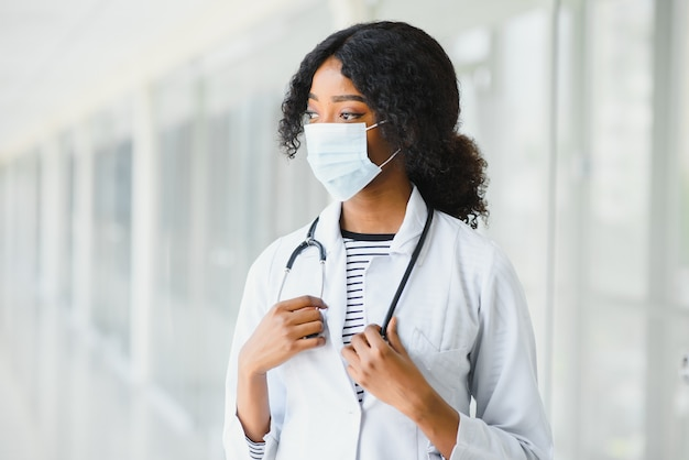 Kobieta amerykański lekarz afrykański, pielęgniarka kobieta ubrana w fartuch medyczny ze stetoskopem i maską. szczęśliwy podekscytowany na sukces pracownik medyczny pozowanie na jasnym tle. koncepcja pandemii, covid 19