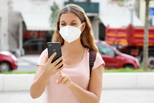 Kobieta ameryki łacińskiej z inteligentny telefon noszenie maski ochronnej twarzy na ulicy