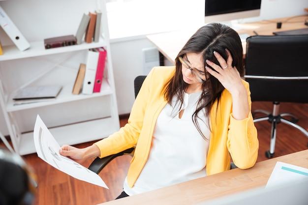 Kobieta analizująca grafikę na papierze w biurze