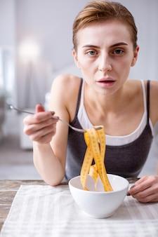 Kobieta anorektyczna. smutna blada kobieta myśli o jedzeniu, mając obsesję na punkcie swojej wagi