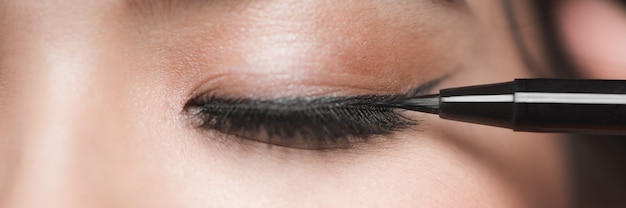 Kobieta aplikująca czarną kreskę do oczu