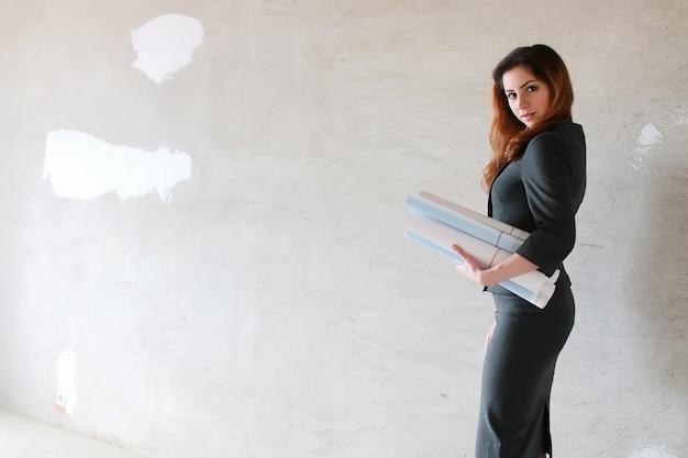 Kobieta architekt na budowie z rysunkami i zeszytem