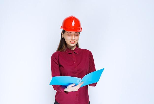 Kobieta architekt w czerwonym kasku czytając folder niebieski na białym tle.