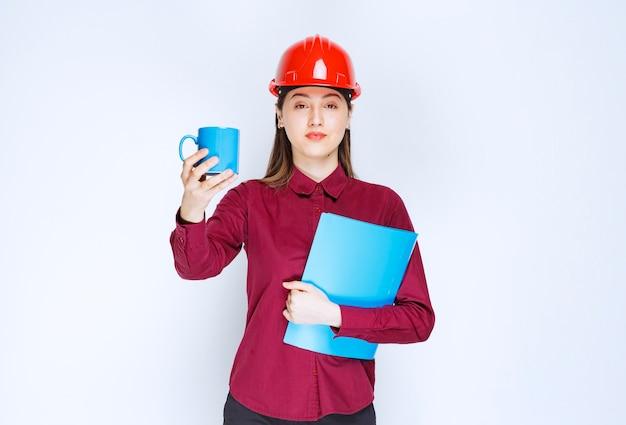 Kobieta architekt w dokumentach czerwony kask w ręku trzyma kawę.