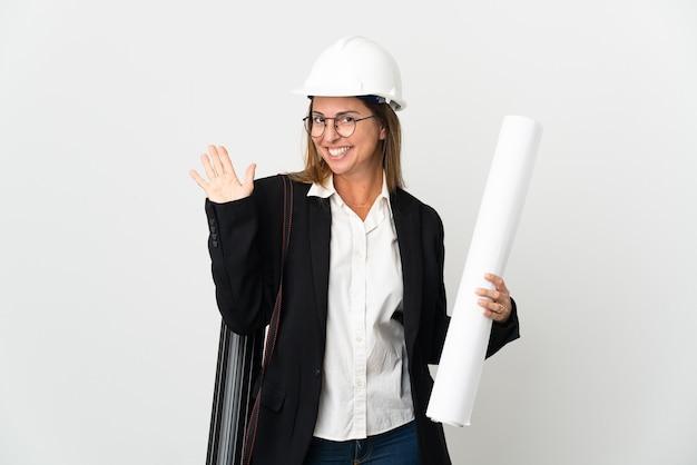 Kobieta architekt w średnim wieku z hełmem i trzymając plany na białym tle