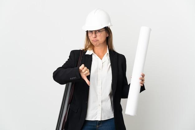 Kobieta architekt w średnim wieku z hełmem i trzymająca plany na białym tle pokazując kciuk w dół z negatywnym wyrazem twarzy