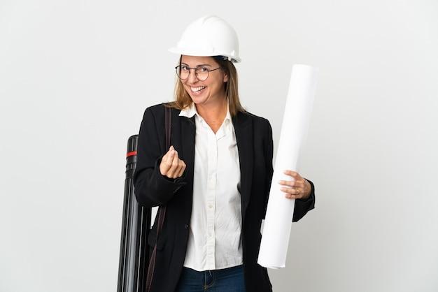 Kobieta architekt w średnim wieku z hełmem i trzymająca plany na białym tle robiąca gest pieniędzy
