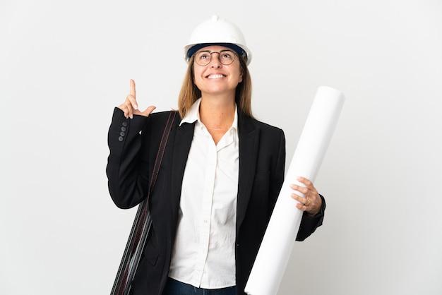 Kobieta architekt w średnim wieku z kaskiem i trzymając plany na białym tle myśląc pomysł wskazując palcem w górę