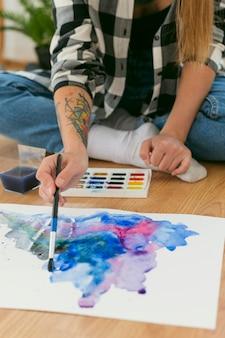 Kobieta artysta malarstwo na podłodze wysoki widok