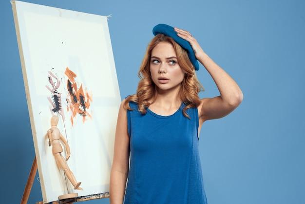 Kobieta artysta malować pędzlem na płótnie sztalugi sztuki edukacji niebieskim tle.