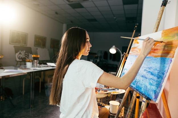 Kobieta artysta malujący obraz na sztalugach farbami olejnymi w swoim warsztacie