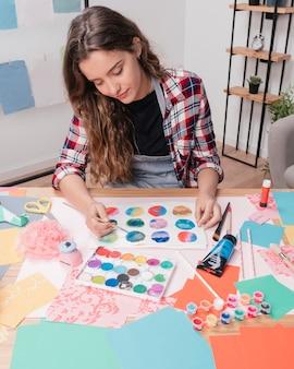 Kobieta artysta maluje abstrakcjonistycznego okrąg na białym papierze
