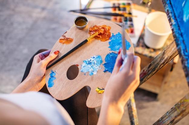 Kobieta artysta miesza kolory oleju na palety mieniu w jej ręce