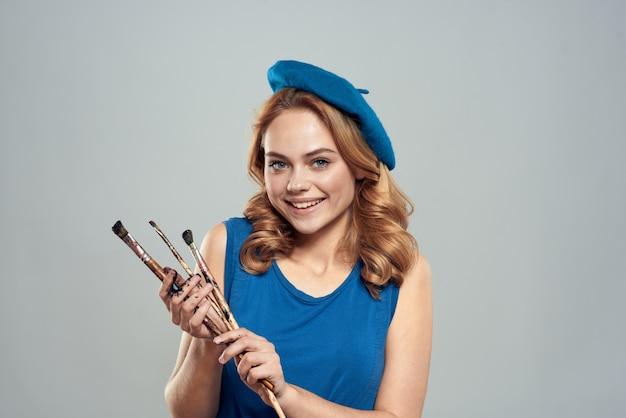 Kobieta artysta szczotka w ręku niebieski beret sukienka hobby art styl życia światło