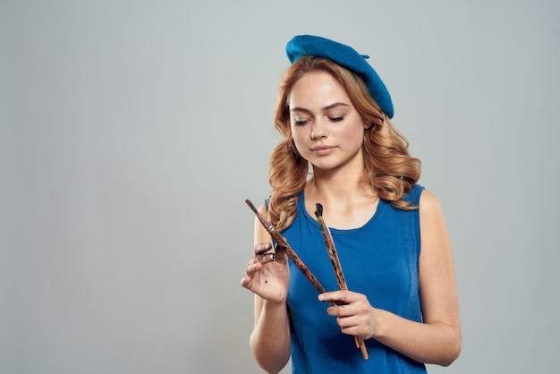 Kobieta artysta szczotka w ręku niebieski beret sukienka hobby sztuka styl życia