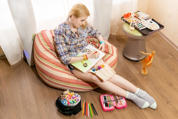 Kobieta-artystka, ilustratorka, która pracuje w domu, robi szkic w zeszycie, siedząc na krześle z fasoli