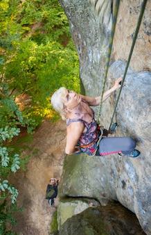 Kobieta arywista wspina się na skalistej ścianie