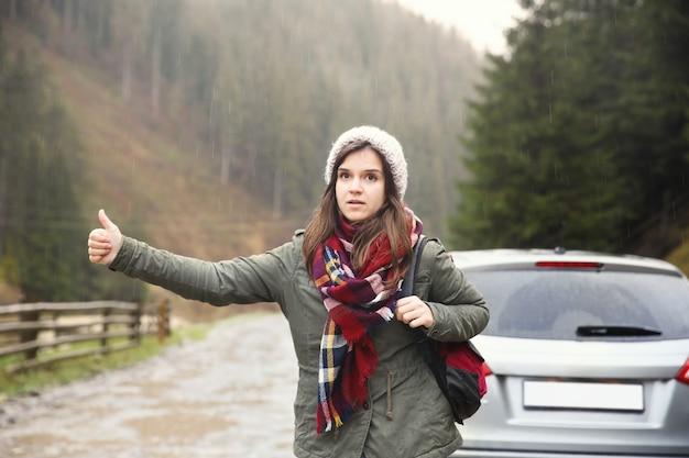 Kobieta autostopem turystycznym samochodu w okolicy