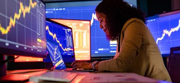 Kobieta azjatyckich udanych profesjonalnych broker inwestor inwestor wpisując na komputerze przenośnym studiując wykres analizy wykresu raport wzrostu wartości przy kupnie sprzedaży transakcji giełdowej handlu online w sali handlowej.