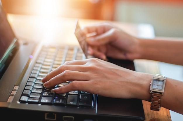 Kobieta azjatykcia używa laptop i kredytowa karta robi zakupy online, selekcyjna ostrość na ręce, miękkiej ostrości i rocznika brzmieniu