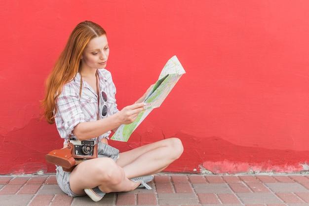 Kobieta bada mapę siedzi w pozycji lotosu