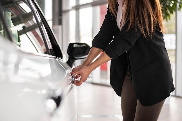Kobieta bada samochód przy przedstawicielstwem handlowym