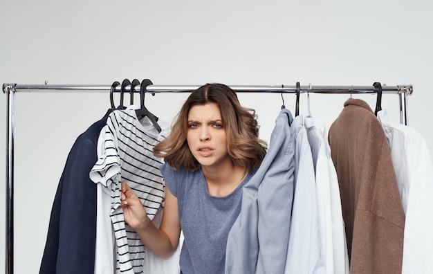 Kobieta bada t-shirt w paski w pobliżu ubrań w szafie na zakupy.