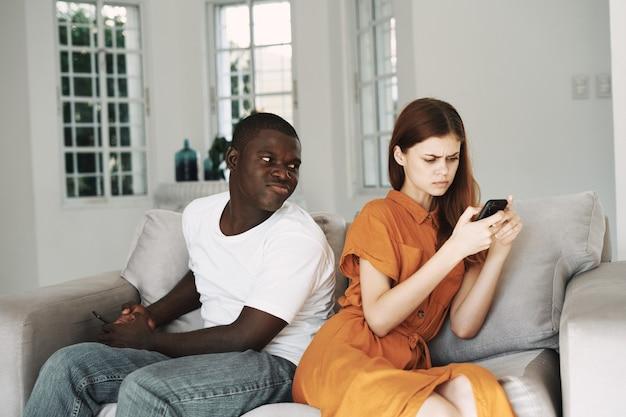 Kobieta bada telefon komórkowy, a obok niego siedzi afrykański mężczyzna