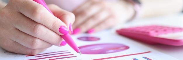 Kobieta bada wykresy biznesowe ze wskaźnikami handlowymi w miejscu pracy