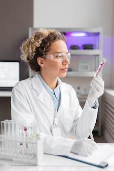 Kobieta badacz w laboratorium z probówkami