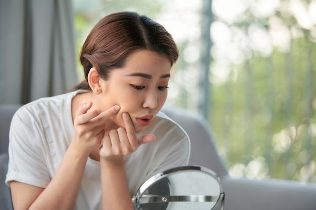 Kobieta badająca twarz w lustrze, problematyczna koncepcja skóry skłonnej do trądziku