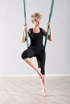 Kobieta balansuje się z powietrznym kocem jogi