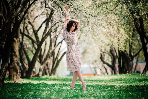 Kobieta baleriny w kwitnącym ogrodzie. różowy. balet. portret tańczącej dziewczyny na świeżym powietrzu. moda i styl