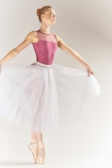 Kobieta baleriny w pointe butach i tutu na jasnym tle pozuje model tańca nogi