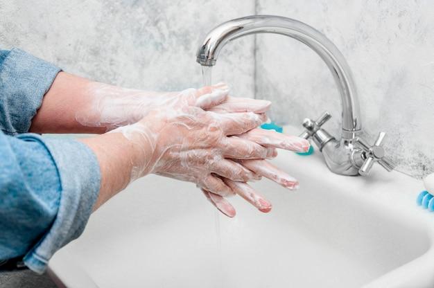 Kobieta bardzo ostrożnie myje rękę mydłem podczas epidemicznego koronawirusa.