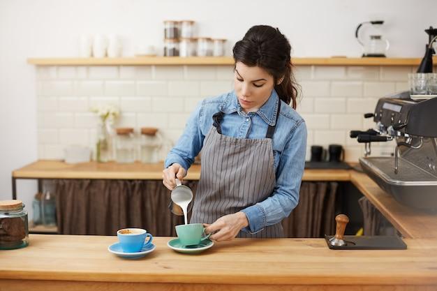 Kobieta barista nalewa mleko, robiąc dwa cappuccino, wyglądając na skoncentrowanego.