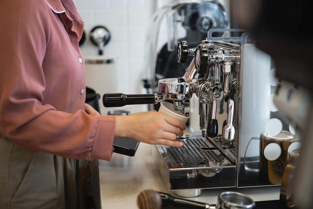 Kobieta barista parzenia kawy w ekspresie do kawy