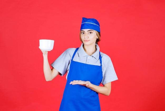 Kobieta barista trzymająca biały duży kubek