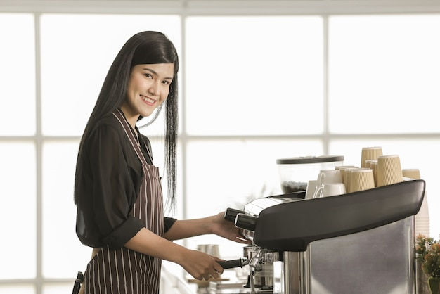 Kobieta barista ubrana w fartuch, stojąca przed ekspresem do kawy i przygotowująca napój w kawiarni z pewnością siebie i przyjaznym sposobem.