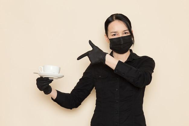 Kobieta barista w czarnych koszulowych spodniach z brązowymi kawowymi suszonymi składnikami herbaty w czarnej sterylnej masce na białej ścianie