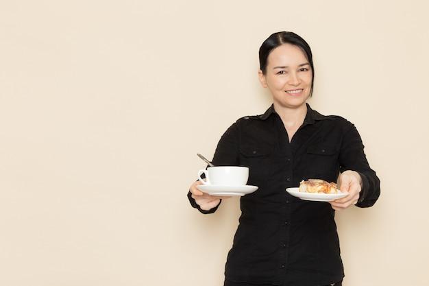 Kobieta barista w czarnych spodniach z brązowymi kawowymi składnikami suszonej herbaty na białej ścianie