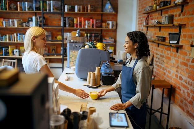 Kobieta barista w fartuchu daje kawę kobiecie w kawiarni. dziewczyna robi świeże espresso w kawiarni, kelner przy ladzie w barze