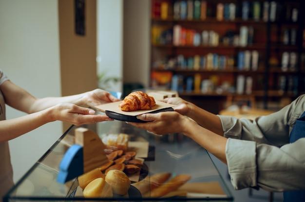 Kobieta barista w fartuchu daje rogalika kobiecie w kawiarni
