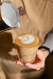 Kobieta barista w fartuchu dekorująca szklankę do kawy mlekiem