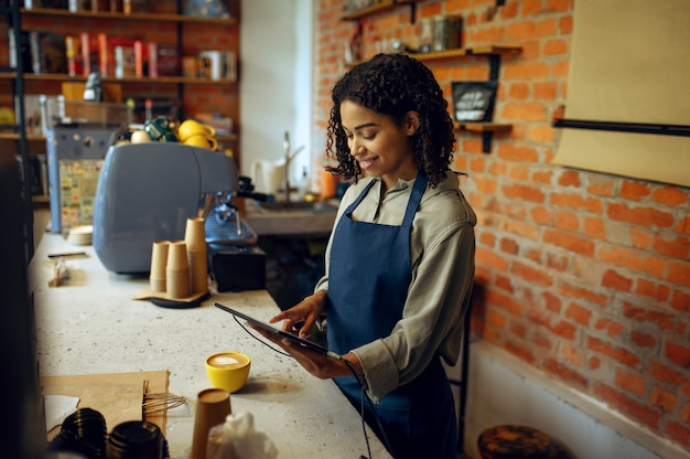 Kobieta barista w fartuchu przyjmuje zamówienia w kawiarni