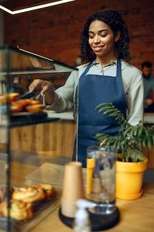 Kobieta barista w fartuchu trzyma talerz z rogalikiem w kawiarni. kobieta wybiera słodycze w kawiarni, kelner przy kasie w barze