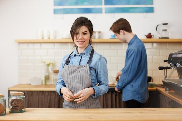Kobieta barista w mundurze uśmiecha się wesoło przyjmując zamówienia.