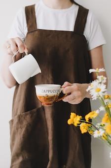 Kobieta barista wlewanie mleka do filiżanki kawy, parzenia kawy