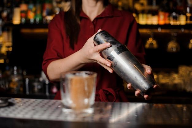 Kobieta barman drżenie drinka za ladą barową