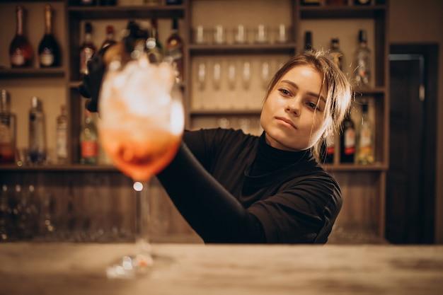 Kobieta barman nalewania champaigne do koktajlu